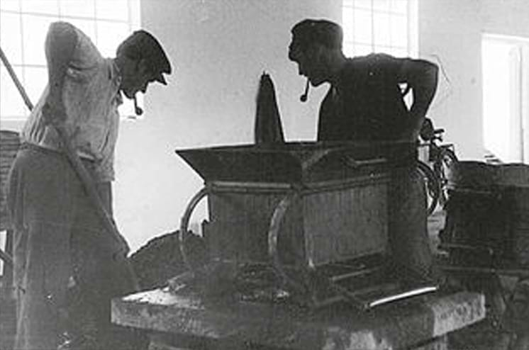 Black and white photo of two men working on a chimney